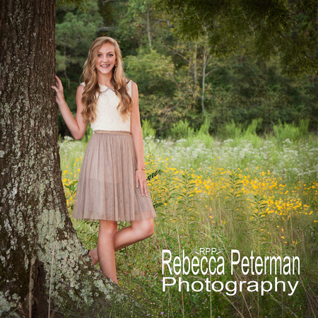Senior Portrait of girl with long blond hair wearing a dress in a field of wildflowers standing beside a tree