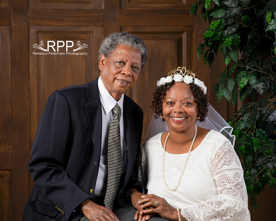 Portrait of African American couple on the occasion of their 50th anniversary.  Man in blue blazer and tie, woman in white dress with flower crown and 50th anniversary golden tiara