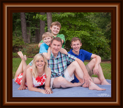 Photo of family on picnic blanket outdoors