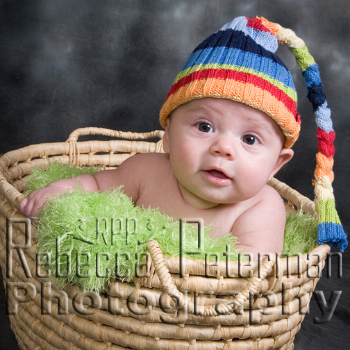 baby in basket with striped hat