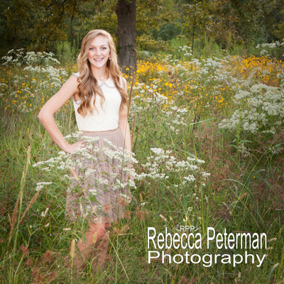 Senior portrait of a girl in a dress standing 1/3 of the way into a field of flowers