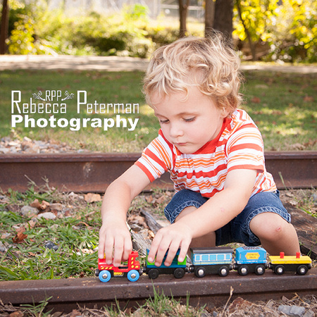 3 year old playing with toy train on real train tracks