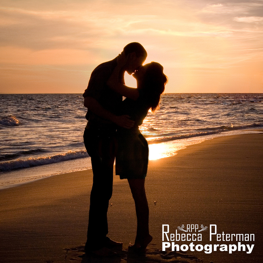 silhouette kiss on beach at sunset