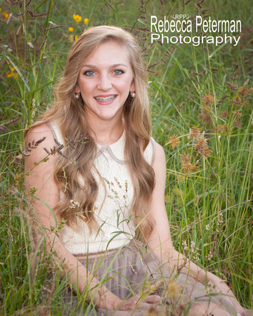 High School Senior with long blond hair in cream colored dress sitting in wildflowers